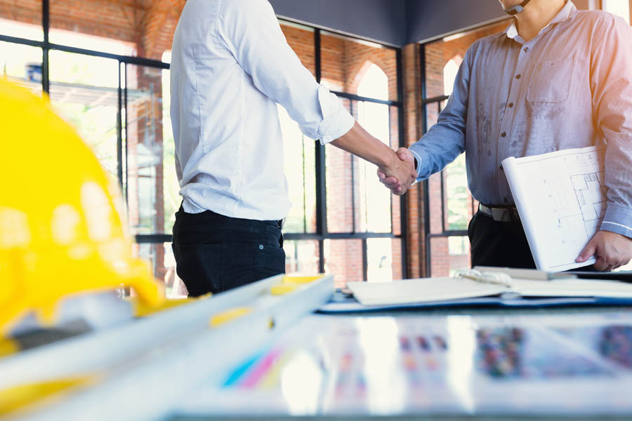 Specialized Business Insurance - Two Contractors Looking Over Building Plans at a Their Office